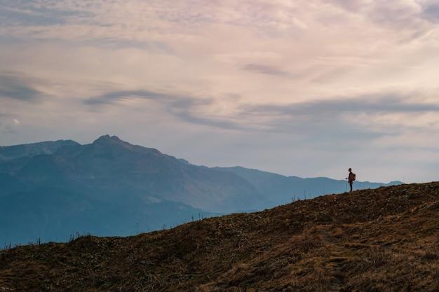 Silhouette di giovane maschio hipster in montagna in autunno. concetto di destinazione di viaggio di scoperta. turista sullo sfondo di alte rocce. sport e concetto di vita attiva.