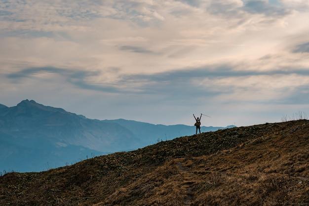 Silhouette di giovane maschio hipster in montagna in autunno con le mani alzate. concetto di destinazione di viaggio di scoperta. turista sullo sfondo di alte rocce. sport e concetto di vita attiva.