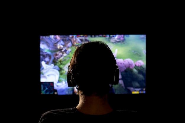 Siluetta di un giovane che gioca video gioco utilizzando le cuffie e la console