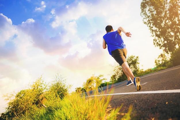 Silhouette di un giovane che corre sprint su strada corridore di fitness corridore in forma durante l'allenamento all'aperto