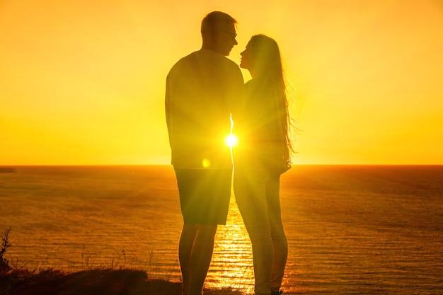 Silhouette di una giovane coppia romantica che si gode una serata su una scogliera a picco sul mare con un rosso