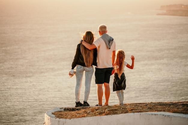 Silhouette di una giovane coppia romantica con un bambino che si gode la serata su una scogliera a picco sul mare
