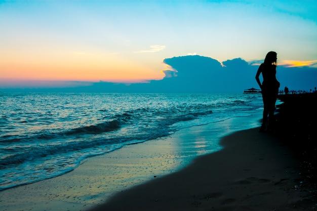 Siluetta di giovane donna sulla spiaggia al tramonto. cielo e mare turchese