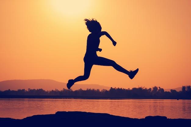 Giovane donna della siluetta che salta nel cielo di alba della natura.