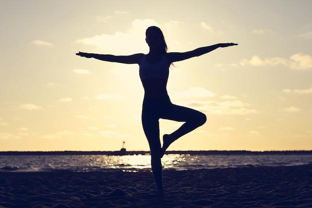 Silhouette giovane donna che pratica yoga sulla spiaggia al tramonto?