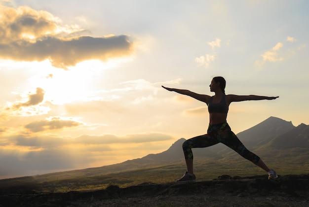 Siluetta di yoga o pilates di pratica della giovane donna al tramonto o all'alba nella bella posizione della montagna.