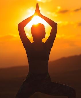 Siluetta di yoga di pratica della giovane donna al tramonto