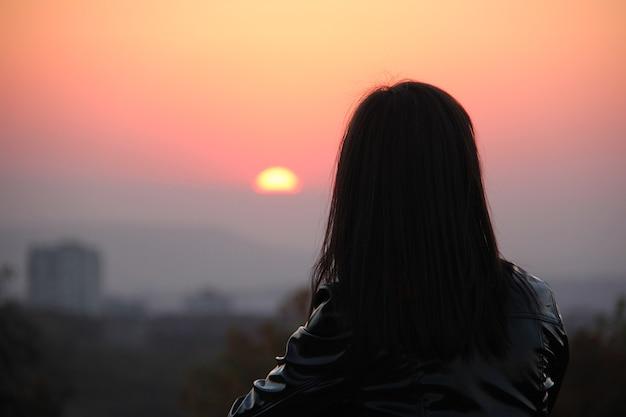 Siluetta di giovane donna nella luce rossa del tramonto che guarda lontano.