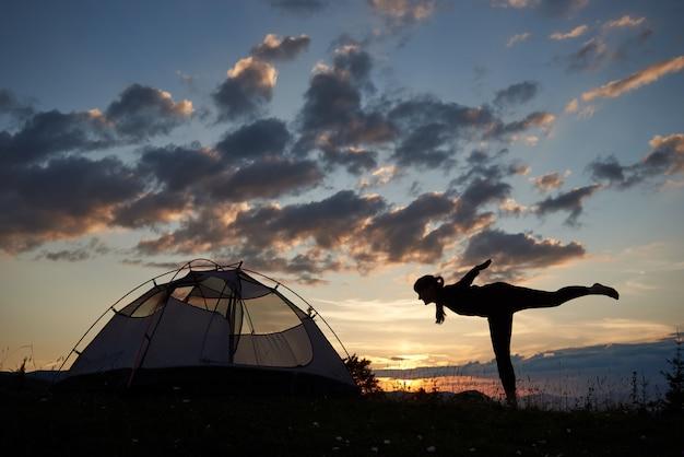 Silhouette di giovane donna accanto alla tenda