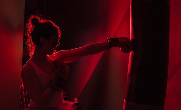Pugile femminile staglia con guantoni da boxe pugno un sacco da boxe in luce al neon rossa su sfondo scuro