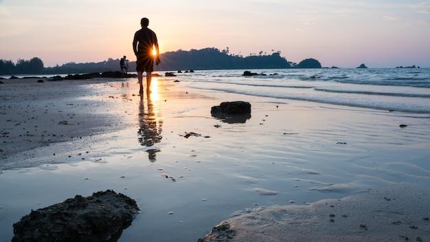 Uomo silhouetted che cammina sulla spiaggia del mare al tramonto