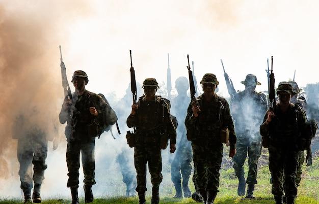 Sagome di soldati dell'esercito nella nebbia contro una squadra di marines al tramonto in azione