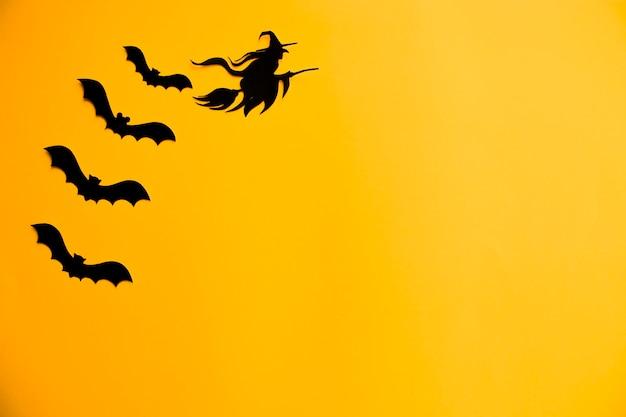 Sagome di pipistrelli neri e strega sulla scopa di carta su sfondo arancione di halloween.