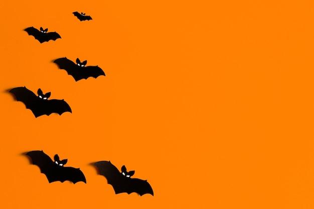 Sagome di pipistrelli di carta nera su uno sfondo arancione per halloween