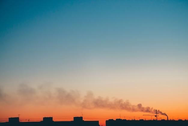 Sagome di edifici e fumo sullo sfondo del cielo arancione al tramonto