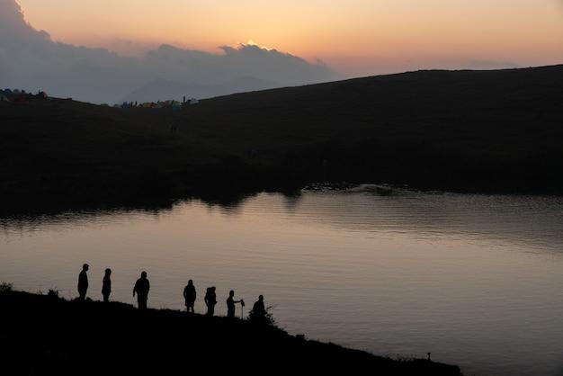 Sagome di campeggiatori in riva al lago al tramonto