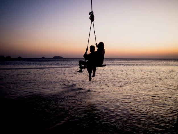 Sagome di altalene di corda per bambini sullo sfondo del mare al tramonto dell'ora d'oro.