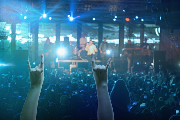 Le sagome della folla da concerto davanti a luci di scena luminose. concerto di una rock band astratta