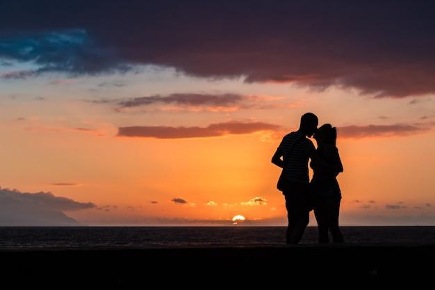 Siluette delle coppie nell'amore che baciano al tramonto