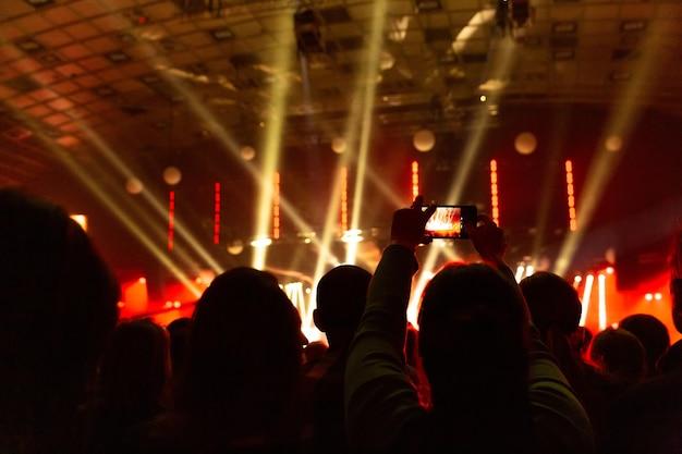 Sagome di folle di spettatori a un concerto con gli smartphone in mano. la scena è splendidamente illuminata da faretti.