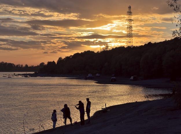 Sagome di pescatori al tramonto la riva del fiume ob un tramonto dorato nel cielo nuvoloso