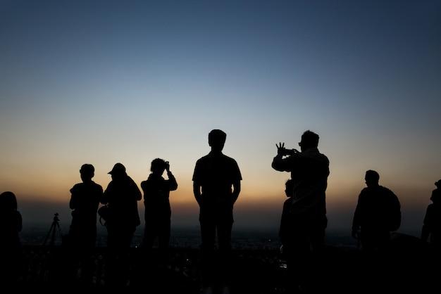 Gruppo di sagome di persone che scattare foto al tramonto a nahagarh fort jaipur.