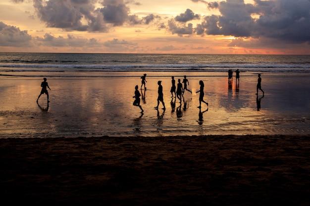 Sagome di ragazzi che giocano a calcio al tramonto sulla spiaggia dell'oceano.