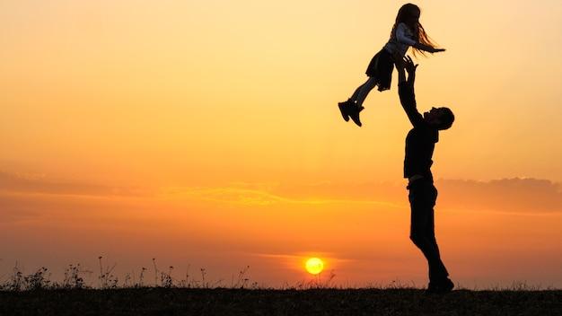 Sagome di bambino felice si precipita nelle mani del padre.