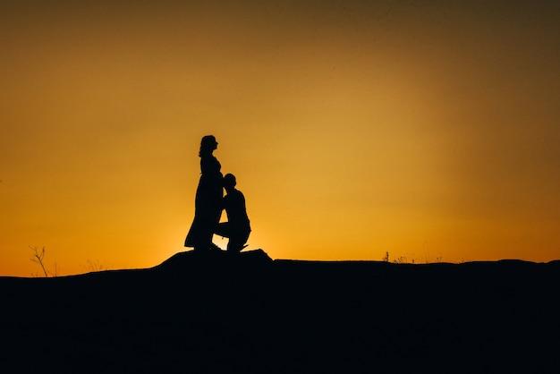 Sagome di una giovane famiglia felice felice contro un tramonto arancione nel deserto