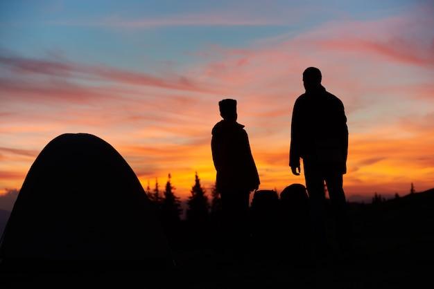 Sagome di un uomo e una donna in piedi vicino alla loro tenda sulla cima di una montagna tramonto mozzafiato