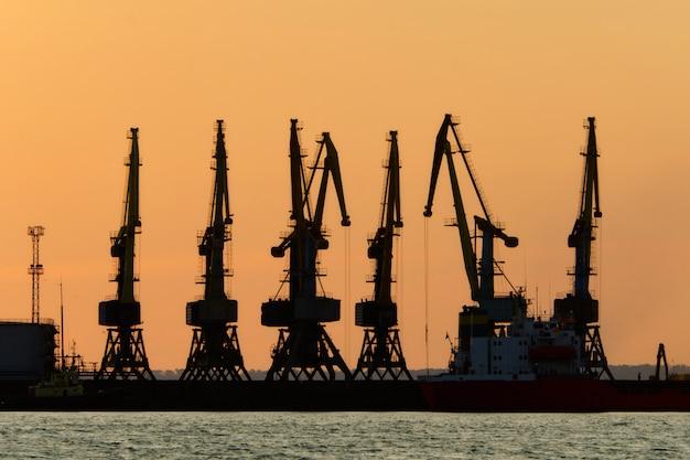 Siluette delle gru del carico del porto al cielo di tramonto