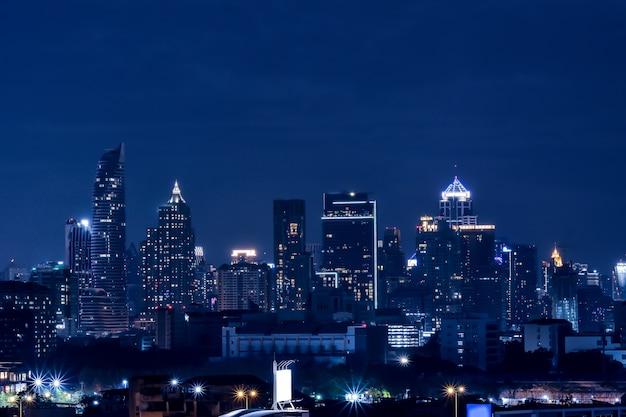 Siluette dei grattacieli nella città scura e sfondo blu