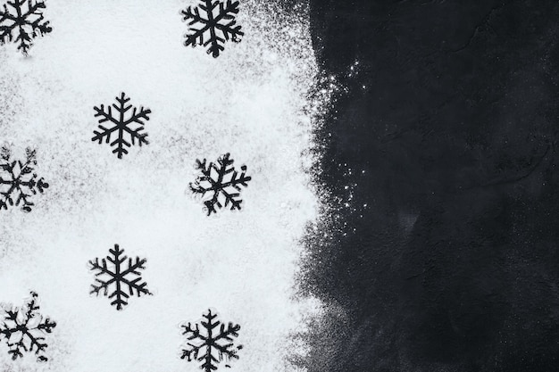 Sagome di fiocchi di neve a base di farina su uno spazio nero della copia.