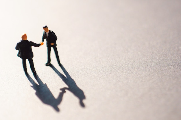 Sagome di due uomini d'affari, probabilmente uomini, che stringono la mano in segno di accordo o accordo. l'incontro si svolge a terra durante il tramonto.