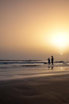 Sagome di due bambini sulla spiaggia al tramonto Foto Premium