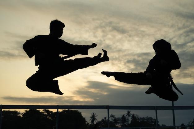 Sagome di due combattenti con calci alla deriva al tramonto