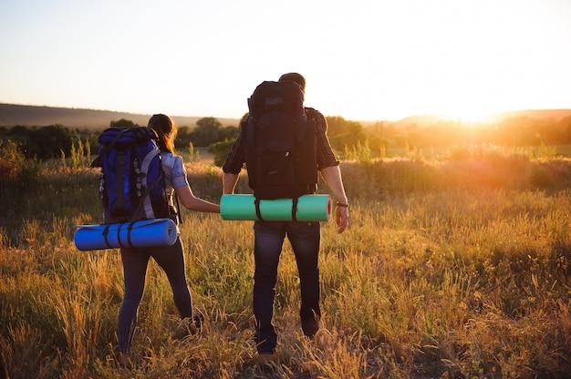 Sagome di due escursionisti con zaini a piedi al tramonto. trekking e godersi la vista del tramonto