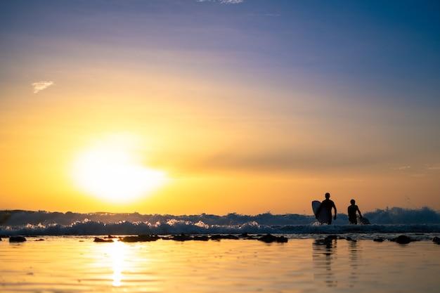 Sagome di due uomini surf al tramonto