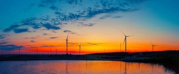 Siluette della centrale elettrica dei generatori eolici sul lago all'alba