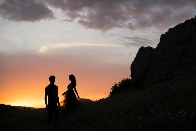 Sagome di una giovane coppia di amanti al tramonto nei raggi del sole al tramonto
