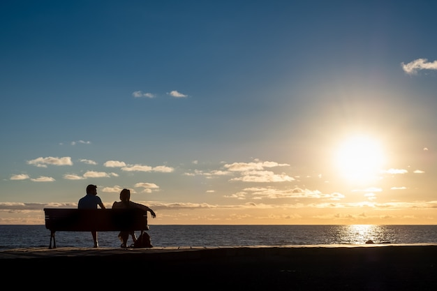 Sagome di una giovane coppia seduta su una panchina di fronte alla costa
