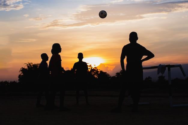 Silhuoette action sport all'aperto di un gruppo di bambini che si divertono a giocare a calcio di strada
