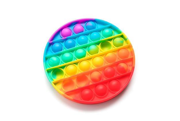 Il popit antistress del giocattolo moderno in silicone avrà una forma rotonda su una superficie bianca