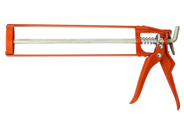Pistola per colla o silicone, isolata su superficie bianca