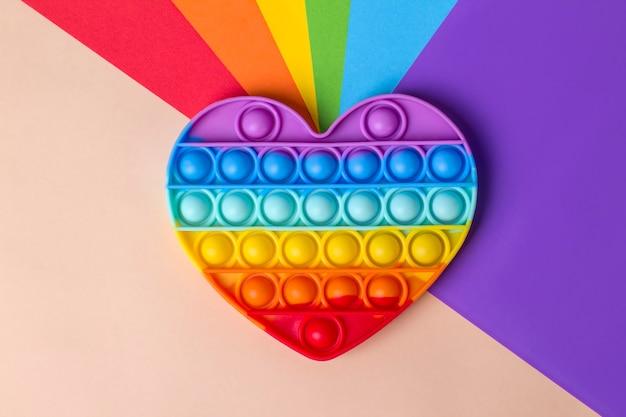Giocattolo a cuore arcobaleno in silicone su uno sfondo con i colori della bandiera lgbt