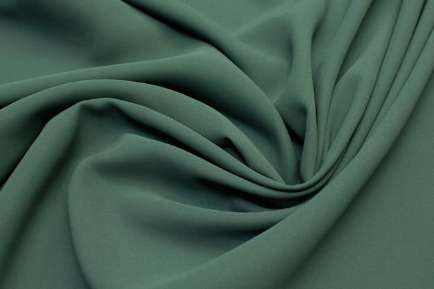 Tessuto di seta di colore verde scuro in una disposizione artistica. struttura,