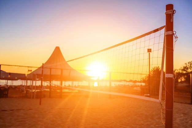 Sillhouette di una rete da pallavolo e alba sulla spiaggia