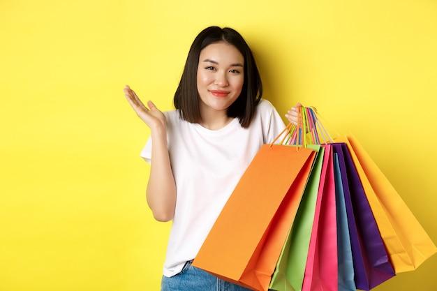 Ragazza asiatica sciocca che mostra le borse della spesa e scrollare le spalle, fare acquisti nei negozi con sconti, in piedi sopra il giallo.