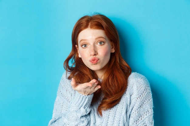 Donna sciocca rossa in maglione, che soffia aria bacio alla macchina fotografica con le labbra arricciate, in piedi su sfondo blu.