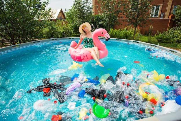 Stupida donna nuota e si diverte in una piscina inquinata. bottiglie e sacchetti di plastica galleggiano vicino a lei.